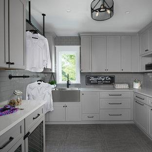 Exemple d'une grand buanderie chic dédiée avec des portes de placard grises, un plan de travail en surface solide, un mur gris, un sol gris, un plan de travail blanc, un évier de ferme et un placard à porte shaker.