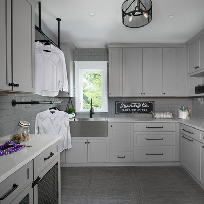 Inspiration for a large transitional gray floor dedicated laundry room remodel in Other with gray cabinets, solid surface countertops, gray walls, white countertops, a farmhouse sink and shaker cabinets