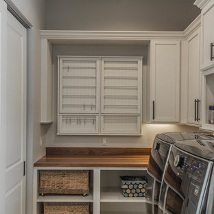 Laundry room - huge rustic l-shaped slate floor and green floor laundry room idea in Detroit with an undermount sink, raised-panel cabinets, medium tone wood cabinets, quartz countertops, beige backsplash, stone tile backsplash, beige walls and a side-by-side washer/dryer