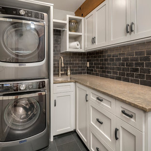 Dedicated laundry room - small rustic l-shaped slate floor dedicated laundry room idea in Seattle with an undermount sink, recessed-panel cabinets, white cabinets, limestone countertops, beige walls and a stacked washer/dryer