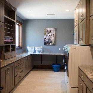 На фото: огромная п-образная универсальная комната в стиле рустика с врезной раковиной, плоскими фасадами, светлыми деревянными фасадами, гранитной столешницей, синими стенами, со стиральной и сушильной машиной рядом, серым полом и разноцветной столешницей с