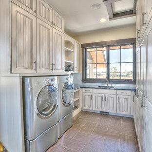Foto på en mycket stor rustik u-formad tvättstuga enbart för tvätt, med en undermonterad diskho, vita skåp, bänkskiva i koppar, beige väggar, skiffergolv, en tvättmaskin och torktumlare bredvid varandra och luckor med infälld panel