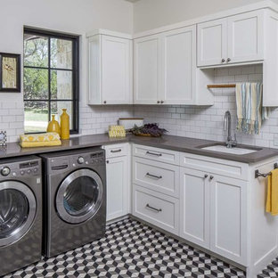Large transitional l-shaped multicolored floor and ceramic floor dedicated laundry room photo in Austin with an undermount sink, shaker cabinets, white cabinets, quartz countertops, white walls and gray countertops