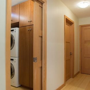 Photo of a small country single-wall utility room in San Francisco with flat-panel cabinets, medium wood cabinets, bamboo floors, a stacked washer and dryer and yellow floor.