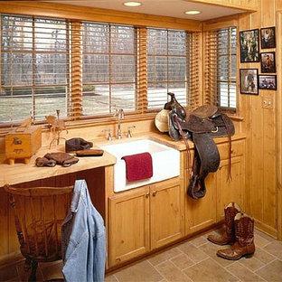 Immagine di una lavanderia multiuso stile rurale di medie dimensioni con lavello stile country, ante in stile shaker, top in legno, pavimento in pietra calcarea e ante in legno scuro