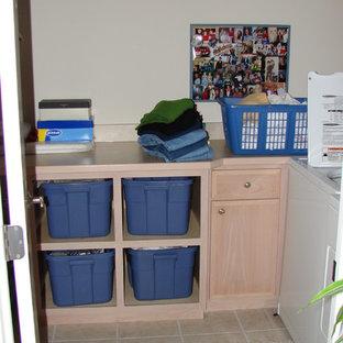 Immagine di una piccola sala lavanderia classica con ante lisce, ante in legno chiaro, top in laminato, pareti beige, lavatrice e asciugatrice affiancate e pavimento con piastrelle in ceramica
