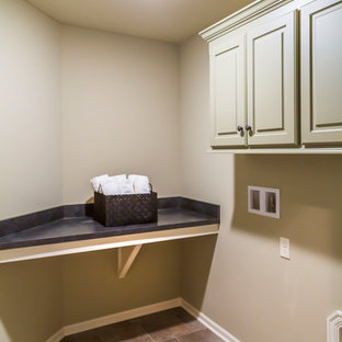 Photo of a medium sized bohemian single-wall laundry cupboard in Kansas City with louvered cabinets, beige cabinets, composite countertops, beige walls, ceramic flooring, a side by side washer and dryer, multi-coloured floors and black worktops.