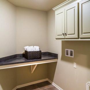 Imagen de armario lavadero lineal, bohemio, de tamaño medio, con armarios con puertas mallorquinas, puertas de armario beige, encimera de acrílico, paredes beige, suelo de baldosas de cerámica, lavadora y secadora juntas, suelo multicolor y encimeras negras