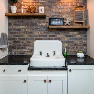 Foto di una lavanderia industriale di medie dimensioni con ante in stile shaker, ante bianche, top in granito, pavimento in ardesia, pareti multicolore e lavello da incasso