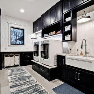 Esempio di un'ampia sala lavanderia moderna con lavello stile country, ante con riquadro incassato, ante nere, top in granito, pareti bianche, pavimento in gres porcellanato, lavatrice e asciugatrice affiancate, pavimento beige e top beige