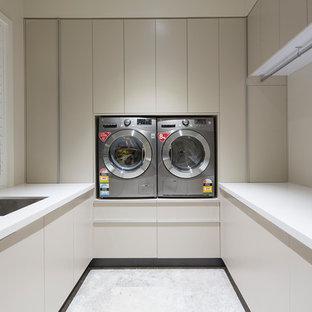 Foto di una piccola sala lavanderia minimal con lavello a doppia vasca, ante lisce, ante beige, top in quarzo composito, pareti beige, pavimento in gres porcellanato e lavatrice e asciugatrice affiancate