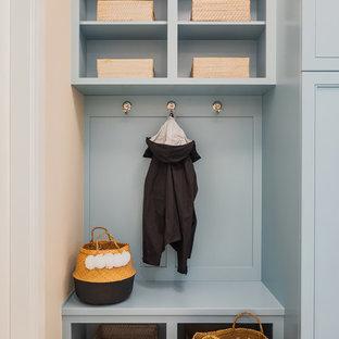 Idéer för ett mellanstort klassiskt vit parallellt grovkök, med en undermonterad diskho, luckor med infälld panel, blå skåp, bänkskiva i kvarts, beige väggar, mellanmörkt trägolv och en tvättmaskin och torktumlare bredvid varandra
