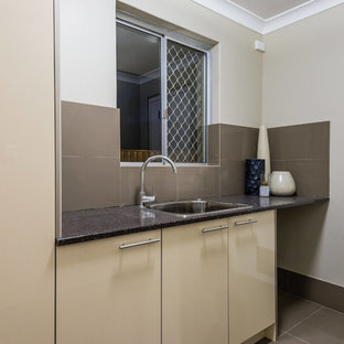 Small contemporary single-wall separated utility room in Perth with beige cabinets, beige walls, porcelain flooring, a stacked washer and dryer, brown floors, black worktops, a single-bowl sink, flat-panel cabinets and composite countertops.
