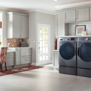 Example of a mid-sized classic single-wall slate floor utility room design in New York with gray cabinets, solid surface countertops, gray walls, a side-by-side washer/dryer and recessed-panel cabinets