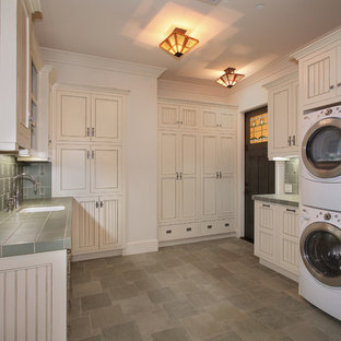 Photo of an expansive arts and crafts u-shaped dedicated laundry room in San Diego with recessed-panel cabinets, white walls, a stacked washer and dryer, grey floor, an undermount sink, tile benchtops, slate floors, green benchtop and beige cabinets.