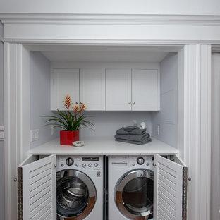 Exemple d'une buanderie linéaire chic de taille moyenne avec un placard, un placard à porte persienne, des portes de placard blanches, un mur bleu, des machines côte à côte, un sol gris et un plan de travail blanc.