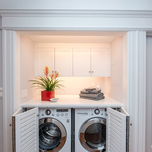 Laundry closet - mid-sized transitional single-wall gray floor laundry closet idea in San Francisco with louvered cabinets, white cabinets, blue walls, a side-by-side washer/dryer and white countertops