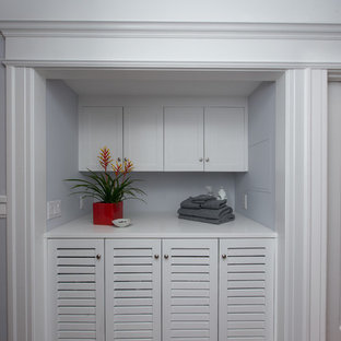 Mid-sized transitional single-wall gray floor laundry closet photo in San Francisco with louvered cabinets, white cabinets, blue walls, a side-by-side washer/dryer and white countertops