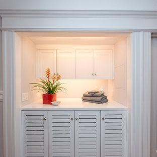 Inredning av en klassisk mellanstor vita linjär vitt liten tvättstuga, med luckor med lamellpanel, vita skåp, blå väggar, en tvättmaskin och torktumlare bredvid varandra och grått golv