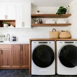 Bild på en mellanstor vintage vita parallell vitt tvättstuga enbart för tvätt, med en nedsänkt diskho, skåp i shakerstil, skåp i mellenmörkt trä, bänkskiva i kvarts, vita väggar, klinkergolv i porslin, en tvättmaskin och torktumlare bredvid varandra och svart golv