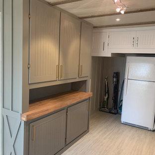 Idéer för att renovera ett mellanstort amerikanskt brun parallellt brunt grovkök, med en nedsänkt diskho, skåp i shakerstil, vita skåp, träbänkskiva, grått stänkskydd, stänkskydd i keramik, grå väggar, vinylgolv, en tvättmaskin och torktumlare bredvid varandra och vitt golv