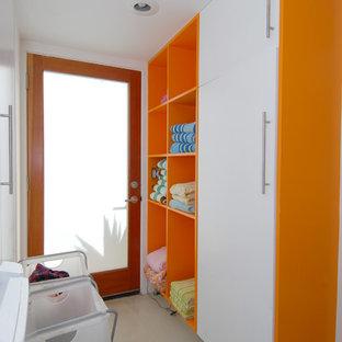 Modern inredning av en parallell tvättstuga, med öppna hyllor och orange skåp