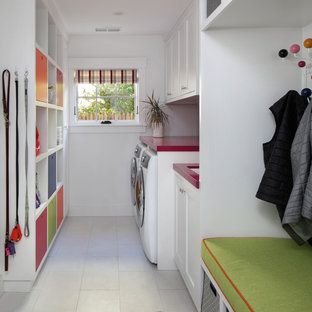 Midcentury utility room in San Francisco with shaker cabinets, white cabinets, solid surface benchtops, white walls, ceramic floors, a side-by-side washer and dryer, white floor and red benchtop.