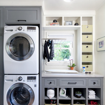 Large transitional single-wall medium tone wood floor laundry room photo in Santa Barbara with shaker cabinets, gray cabinets, white walls, a stacked washer/dryer and gray countertops