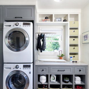 Large classic single-wall utility room in Santa Barbara with shaker cabinets, grey cabinets, white walls, medium hardwood flooring, a stacked washer and dryer and grey worktops.