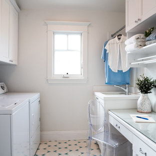 Dedicated laundry room - small coastal galley ceramic tile and blue floor dedicated laundry room idea in Los Angeles with an undermount sink, shaker cabinets, white cabinets, glass countertops, white walls, a side-by-side washer/dryer and white countertops