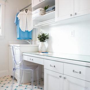 Inspiration för små maritima parallella vitt tvättstugor enbart för tvätt, med en undermonterad diskho, skåp i shakerstil, vita skåp, bänkskiva i glas, klinkergolv i keramik, en tvättmaskin och torktumlare bredvid varandra, blått golv och vita väggar
