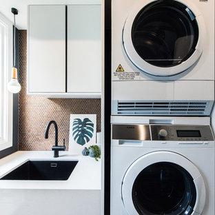 Ispirazione per una sala lavanderia minimal di medie dimensioni con lavello sottopiano, ante lisce, ante bianche, top in quarzo composito, pareti nere e lavatrice e asciugatrice a colonna