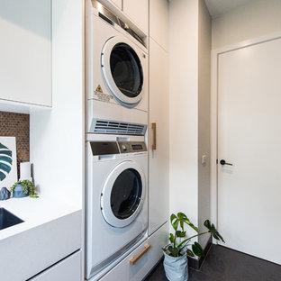 Idéer för en mellanstor modern linjär tvättstuga enbart för tvätt, med en undermonterad diskho, släta luckor, vita skåp, bänkskiva i kvarts, svarta väggar och en tvättpelare