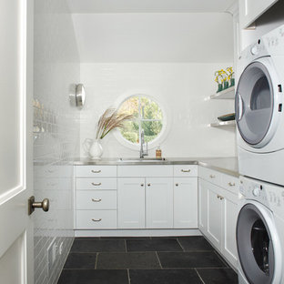 Inspiration for a country slate floor laundry room remodel in Detroit with an undermount sink, shaker cabinets, white cabinets, stainless steel countertops, white walls and a stacked washer/dryer