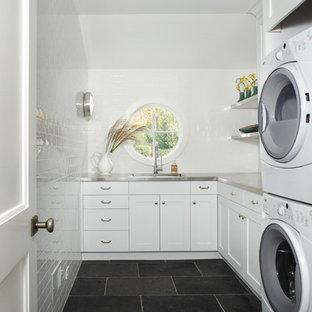 Cette photo montre une buanderie nature avec un évier encastré, un placard à porte shaker, des portes de placard blanches, un plan de travail en inox, un mur blanc, un sol en ardoise et des machines superposées.