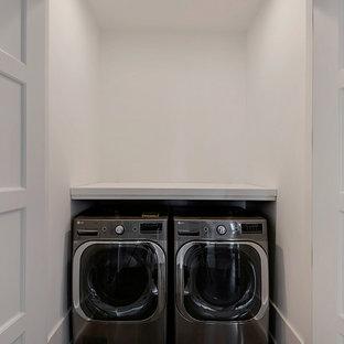 Inspiration för små klassiska linjära små tvättstugor, med träbänkskiva, vita väggar och en tvättmaskin och torktumlare bredvid varandra