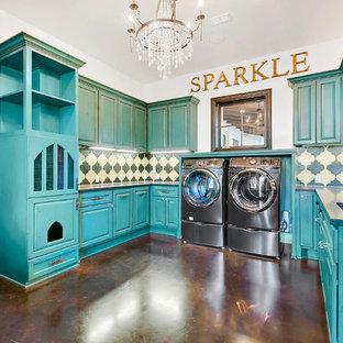Immagine di una sala lavanderia mediterranea con lavello sottopiano, ante con bugna sagomata, ante blu, pareti bianche, pavimento in cemento, lavatrice e asciugatrice affiancate e pavimento marrone