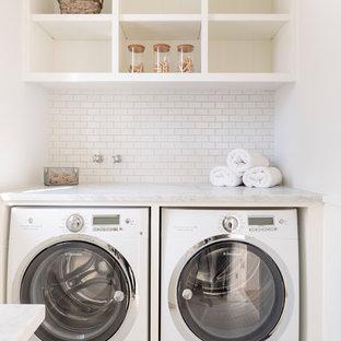 Bild på en maritim tvättstuga, med en tvättmaskin och torktumlare bredvid varandra, öppna hyllor och vita skåp