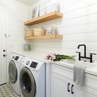 Exempel på en maritim vita linjär vitt tvättstuga enbart för tvätt, med en undermonterad diskho, skåp i shakerstil, vita skåp, vita väggar, en tvättmaskin och torktumlare bredvid varandra och flerfärgat golv