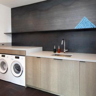 Foto di una sala lavanderia moderna di medie dimensioni con lavello sottopiano, ante lisce, ante in legno scuro, top in quarzo composito, paraspruzzi grigio, paraspruzzi con piastrelle di metallo, pareti bianche, parquet scuro, lavatrice e asciugatrice affiancate, pavimento grigio e top bianco