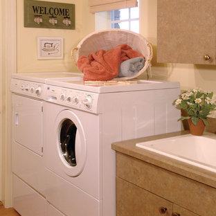 Foto di una grande sala lavanderia country con lavello da incasso, ante lisce, ante marroni, top in superficie solida, pavimento in legno massello medio, lavatrice e asciugatrice affiancate e pareti beige