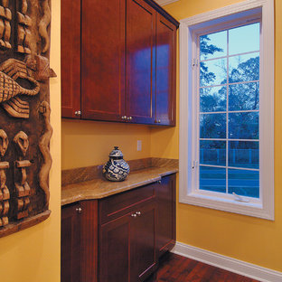 This is an example of a large beach style galley laundry cupboard in Miami with shaker cabinets, dark wood cabinets, granite worktops, dark hardwood flooring and orange walls.