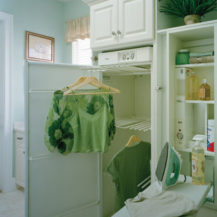 Idées déco pour une buanderie linéaire classique dédiée avec un placard avec porte à panneau surélevé, des portes de placard blanches, un mur bleu et un sol en carrelage de céramique.
