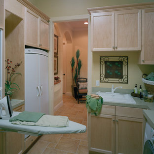 This is an example of a large mediterranean galley separated utility room in Miami with a built-in sink, recessed-panel cabinets, light wood cabinets, laminate countertops, travertine flooring, a side by side washer and dryer and beige walls.