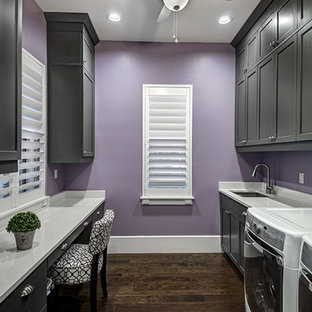 Photo of a large arts and crafts galley utility room in Miami with an undermount sink, recessed-panel cabinets, grey cabinets, quartzite benchtops, purple walls, dark hardwood floors and a side-by-side washer and dryer.