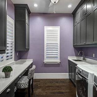 Amerikansk inredning av ett stort parallellt grovkök, med en undermonterad diskho, luckor med infälld panel, grå skåp, bänkskiva i kvartsit, lila väggar, mörkt trägolv och en tvättmaskin och torktumlare bredvid varandra