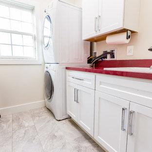 Immagine di una piccola sala lavanderia design con lavello da incasso, ante con riquadro incassato, ante bianche, top in laminato, pareti bianche, pavimento in gres porcellanato, lavatrice e asciugatrice a colonna, pavimento grigio e top rosso