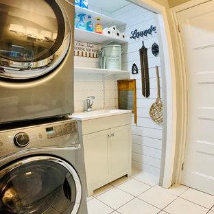 Ispirazione per un piccolo ripostiglio-lavanderia nordico con lavello integrato, ante in stile shaker, ante grigie, top in quarzo composito, pareti bianche, pavimento con piastrelle in ceramica, lavatrice e asciugatrice a colonna, pavimento bianco e top bianco