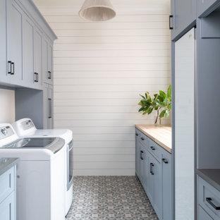 Aménagement d'une grand buanderie parallèle classique dédiée avec un placard à porte shaker, des portes de placard bleues, un plan de travail en bois, un mur blanc, un sol en carrelage de porcelaine, des machines côte à côte, un sol gris et un plan de travail beige.
