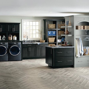 Inspiration for a large transitional gray floor utility room remodel with black cabinets, gray walls and a side-by-side washer/dryer
